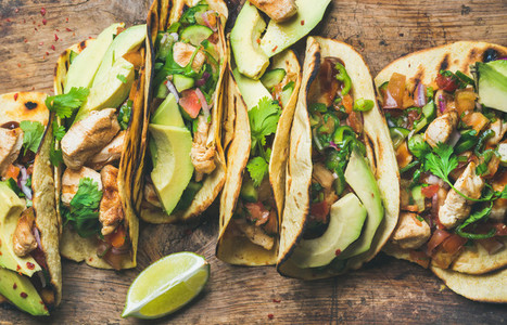 Tacos with grilled chicken  avocado  fresh salsa sauce and limes