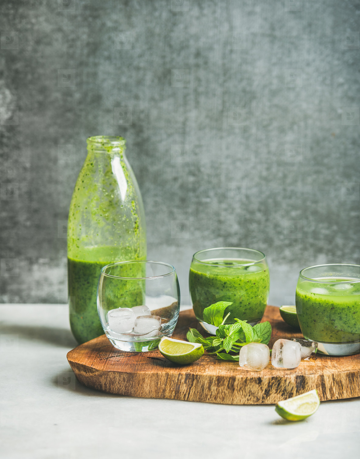 Fresh green smoothie with ice  mint and lime on board