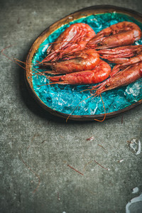 Raw uncooked red shrimps on ice in turquoise ceramic tray