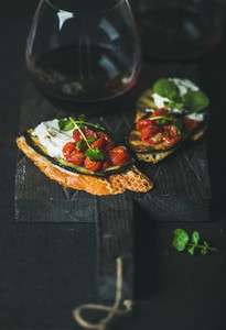 Red wine in glass and brushetta with vegetables  cream cheese  arugula
