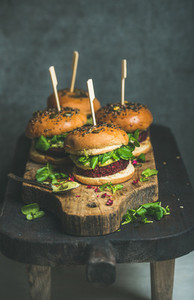 Healthy homemade vegan burger with beetroot quinoa patty on wooden table