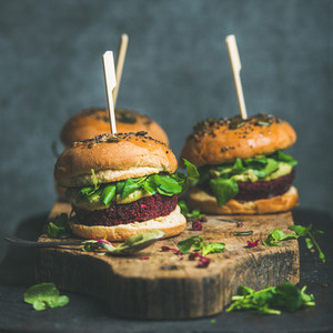 Healthy vegan burger with beetroot quinoa patty and arugula square crop