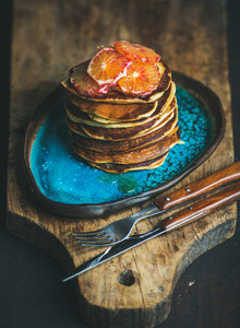 Pancakes with honey and bloody orange slices on blue plate