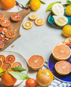 Natural fresh citrus fruits in ceramic plates over grey background