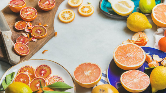 Natural fresh citrus fruits in ceramic plates and wooden board