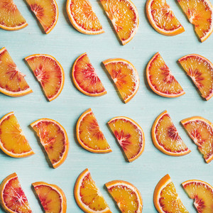 Fresh juicy blood orange slices over blue background  square crop