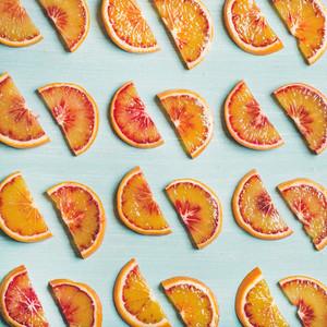 Fresh juicy blood orange slices over blue background square crop
