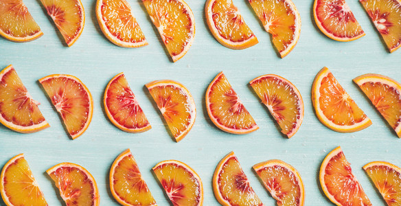 Fresh juicy blood orange slices over blue background  wide format