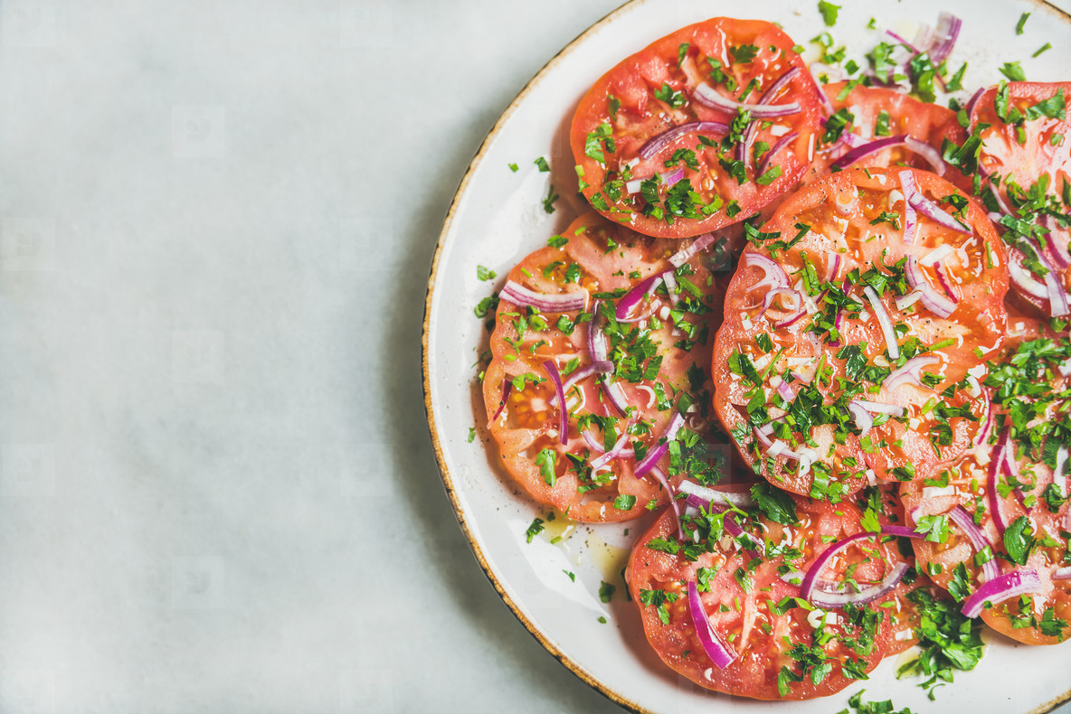 Fresh heirloom tomato  parsley and onion salad in white plate