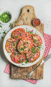 Fresh tomato  parsley and onion salad on shabby wooden board