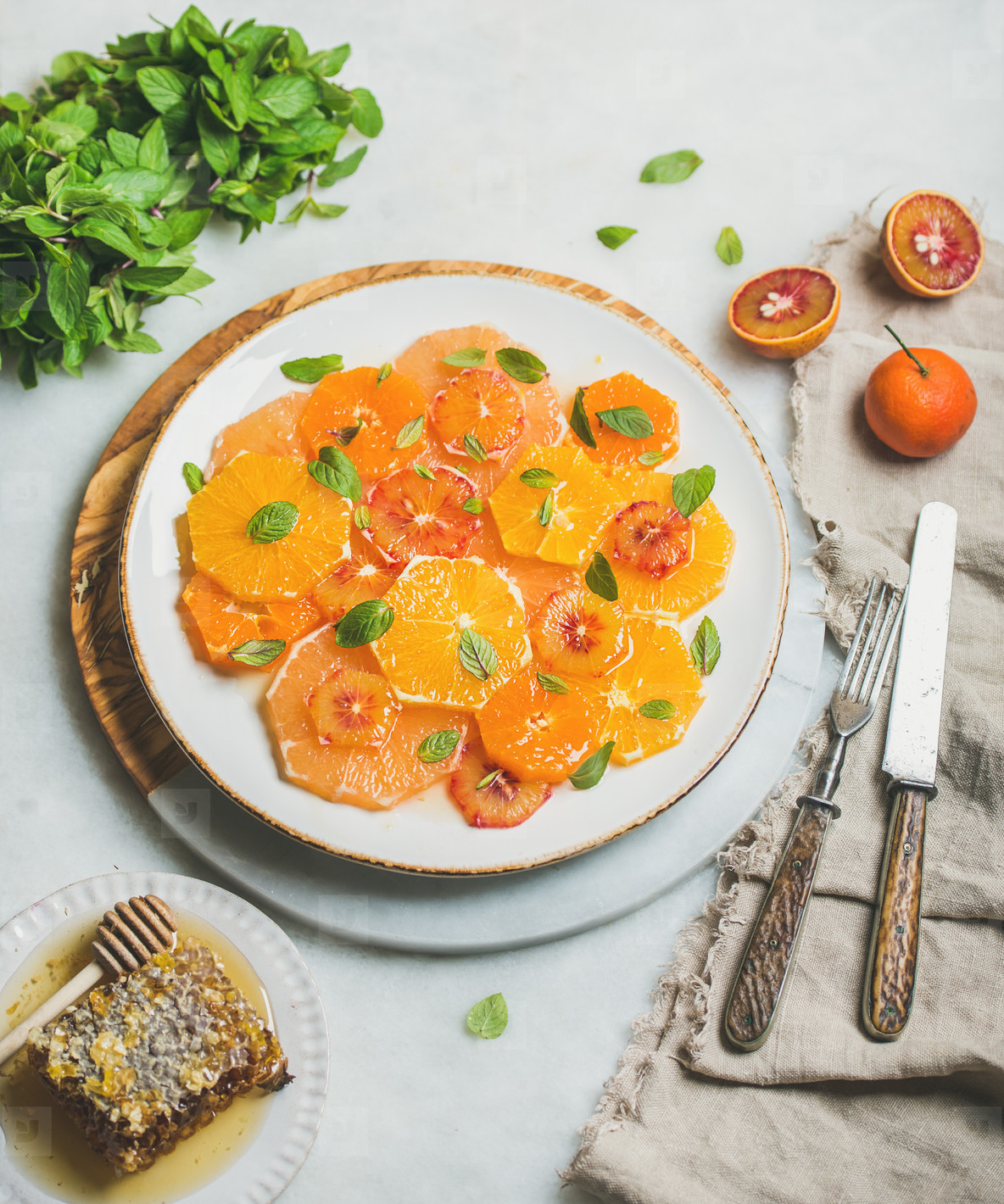 Fresh mixed citrus fruit salad with mint leaves and honey