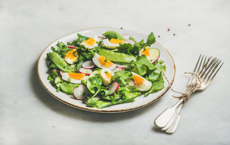 Healthy spring green salad in white plate over grey background