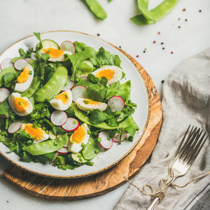 Green salad with radish  boiled egg  arugula  green pea  mint
