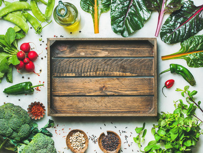 Fresh greens  vegetables and grains with wooden box in center