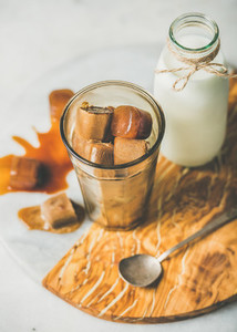 Glass with frozen coffee ice cubes and milk on board