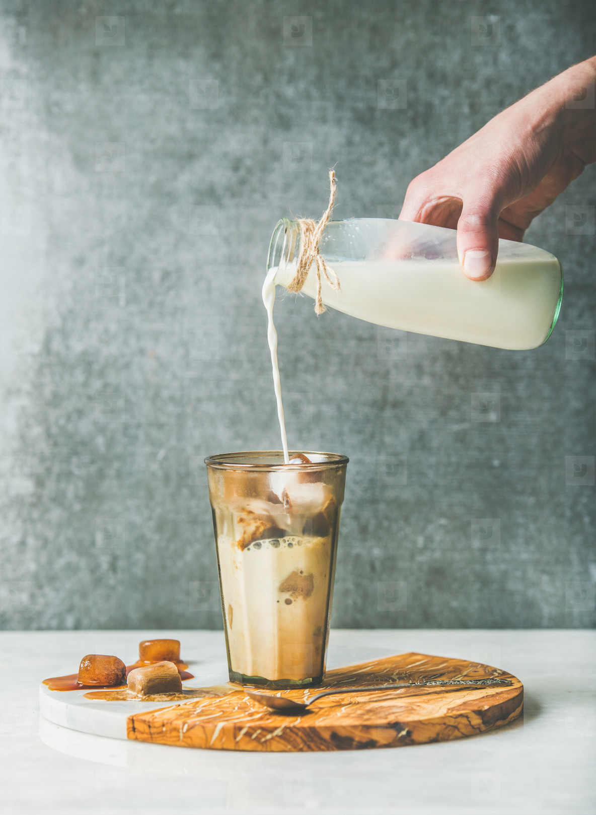 Man s hand pouring milk to Iced latte caramel coffee cocktail