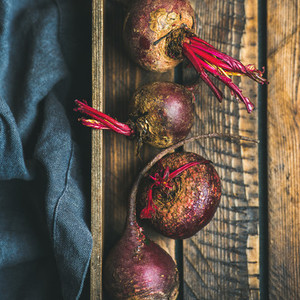 Raw organic purple beetroots in wooden box  square crop