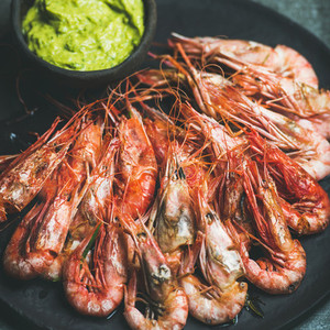 Roasted red shrimps with guacamole avocado sauce in black plate