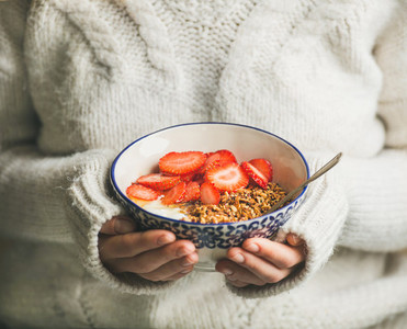 Healthy breakfast yogurt  granola  strawberry bowl in hands of woman