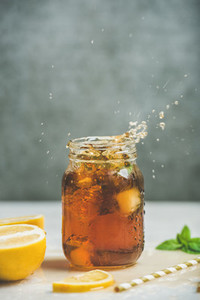 Iced tea with bergamot and mint in jar with splashes