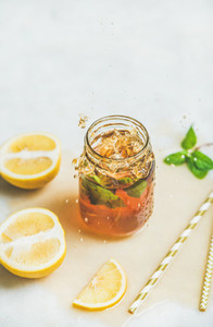 Summer cold Iced tea with lemon and herbs copy space