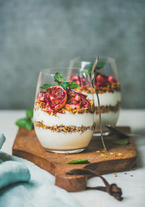 Healthy breakfast glasses with yougurt granola and orange