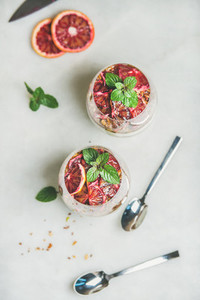 Healthy breakfast with yogurt granola orange layered parfait in glasses
