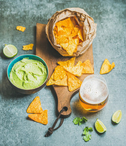 Mexican corn chips  fresh guacamole sauce and beer  concrete background