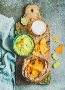 Mexican corn chips fresh guacamole sauce and beer top view