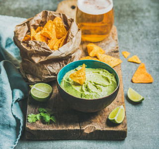 Fresh guacamole sauce in blue ceramic bowl  corn chips  beer