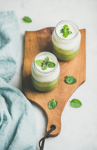 Ombre layered green smoothies in glass jars on wooden board