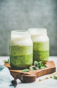 Ombre layered green smoothies with mint in glass jars