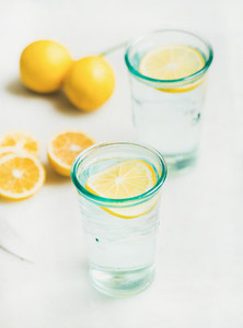 Detox lemon water in glasses served with fresh lemons