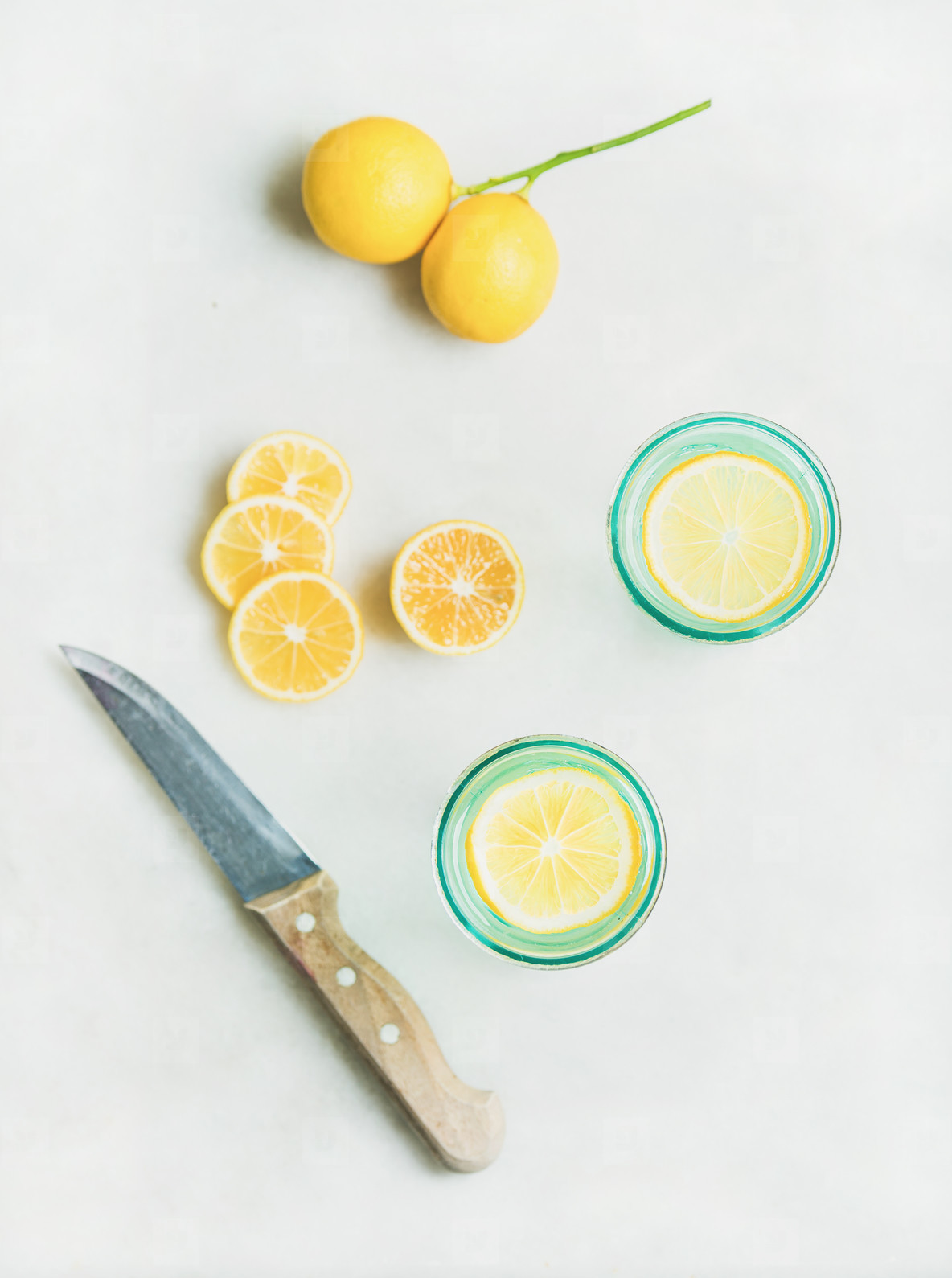 Morning detox lemon water in glasses  marble background  top view