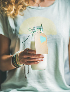 Young blond woman holding bottle of dairy free almond milk
