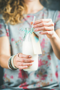 Young woman holding bottle of dairy free almond milk