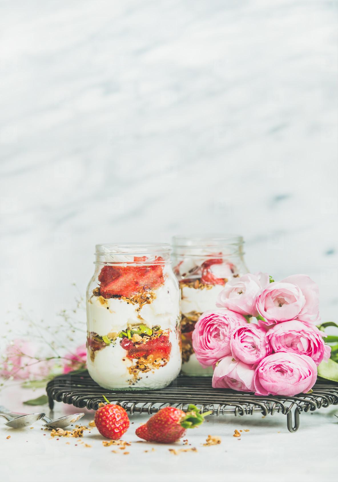 Greek yogurt  granola  fresh strawberry breakfast in jars  raninkulus flowers