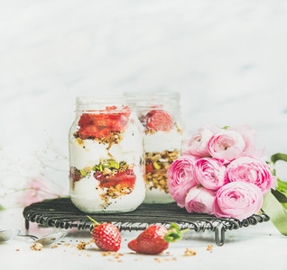 Healthy vegan spring breakfast jars with pink raninkulus flowers