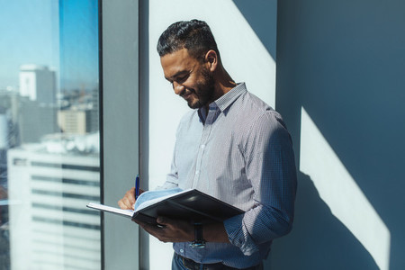 Business investor writing in diary standing at the window in off