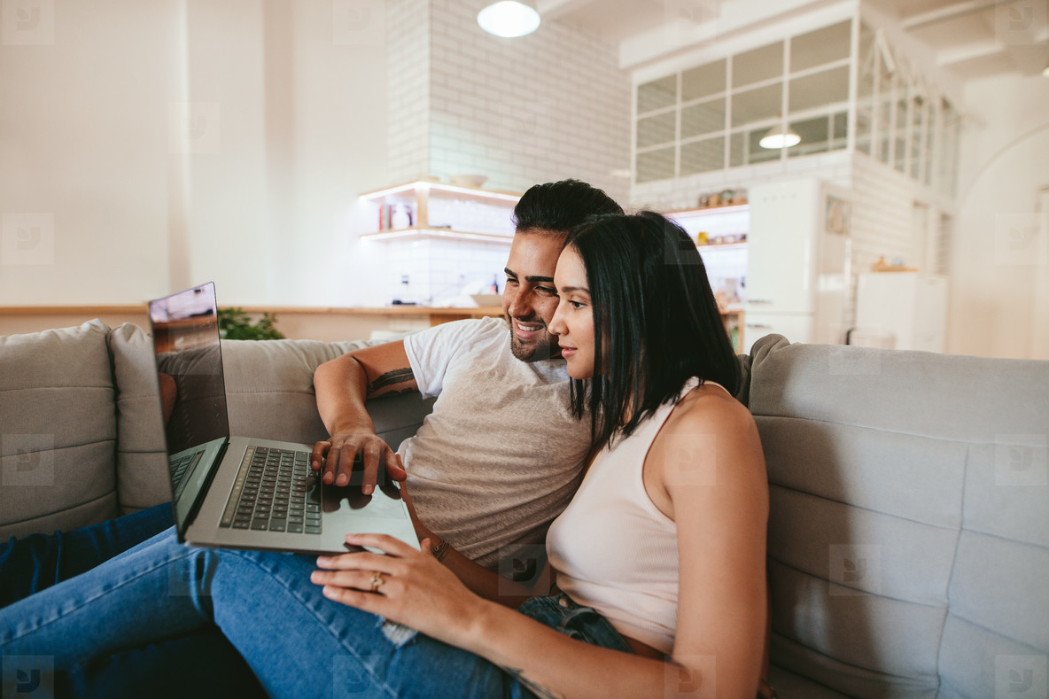 Young couple relaxing on couch with laptop