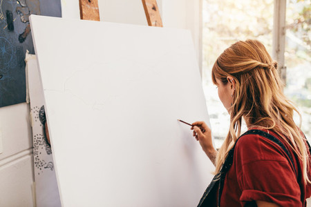 Female artist drawing on canvas