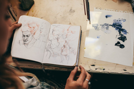 Female artist looking at sketches in her studio