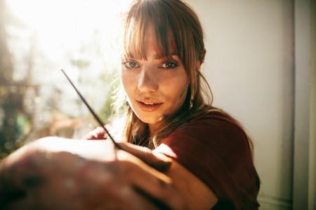 Beautiful female painter looking at camera