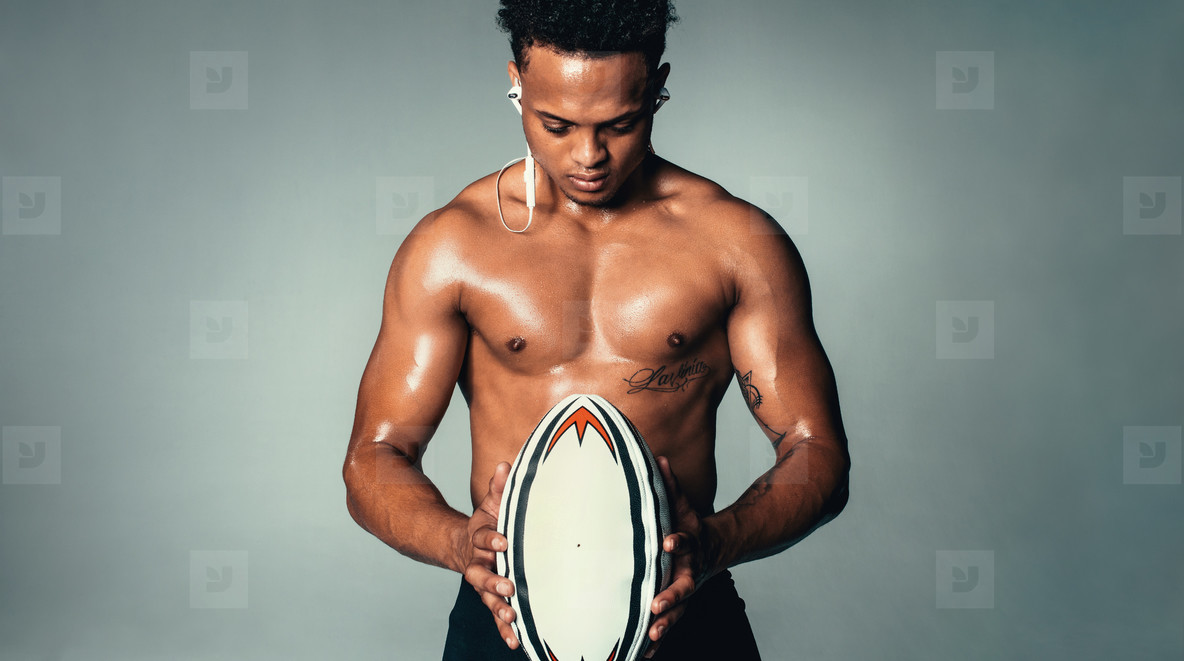 Model with strong body holding rugby ball