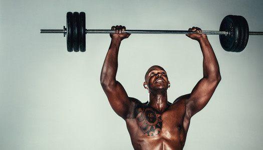 Muscular african man exercising with barbell