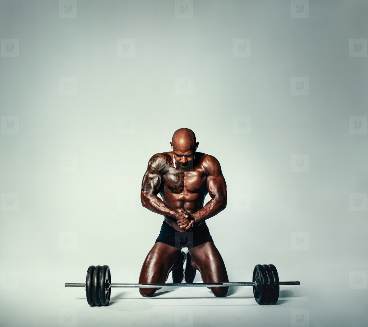 Muscular young man working out with heavy weights