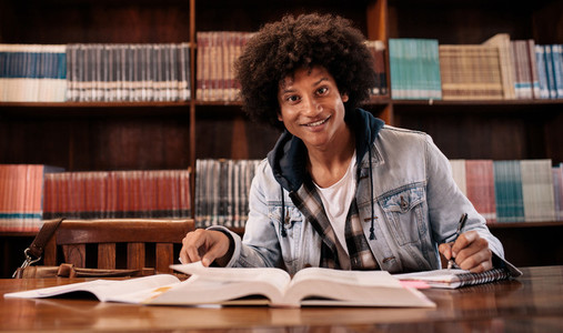 Young confident student studying in library
