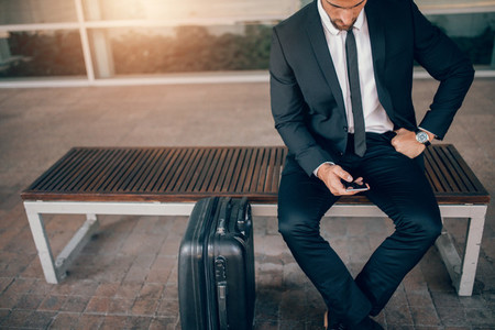 Businessman sitting on bench with suitcase and using smart phone