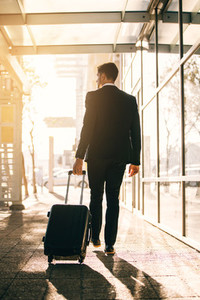 Young businessman walking with suitcase outside airport building