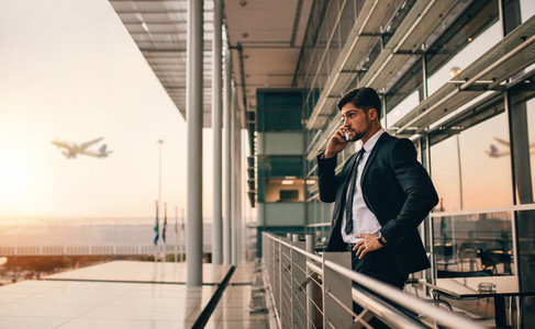Businessman on airport lounge balcony making phone call